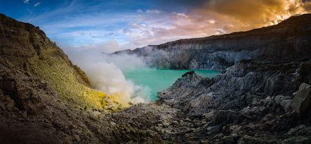 Kawah Ijen volcano with green lake on blue sky background at morning in East Java, Indonesia. Stock Photo