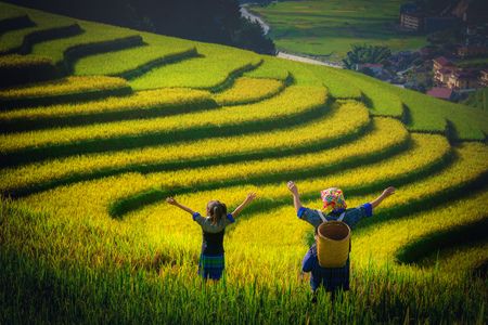 女性農民と Mu 倉チャイ、YenBai、ベトナムで夕暮れの棚田の田んぼの上に腕を上げる娘。