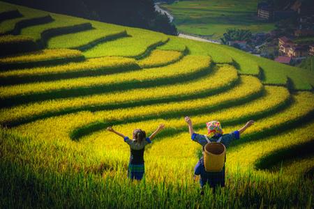 Women farmer and daughter raising arm on Rice fields terraced at sunset in Mu Cang Chai, YenBai, Vietnam. Standard-Bild