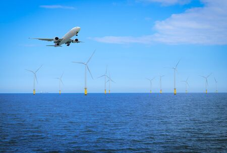 Offshore Wind Turbine with plane fly in a Wind farm under construction off coast of England. Фото со стока
