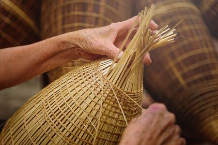 Vietnamese fishermen are doing basketry for fishing equipment at morning in Thu Sy Village, Vietnam. Stock Photo