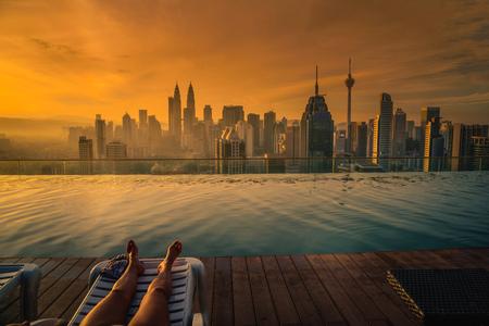여행자 여자는 태양 침대에 수영장 근처 지붕에 수영장 쿠알라 룸푸르, 말레이시아에서 일출 호텔의 상단. 스톡 콘텐츠