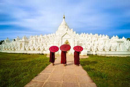Three Asian young monk holding red umbrellas on the Mya Thein Tan Pagoda at Mingun, Mandalay Myanmar.