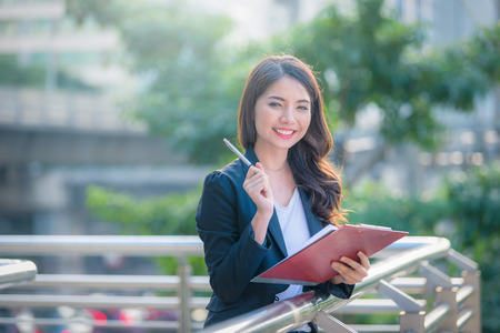 Portrait of business woman happy smile holding check list on clipboard and pen. 免版税图像