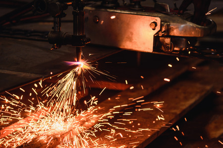 Worker cutting steel plate with acetylene welding cutting torch and bright sparks in steel industry. Stock Photo