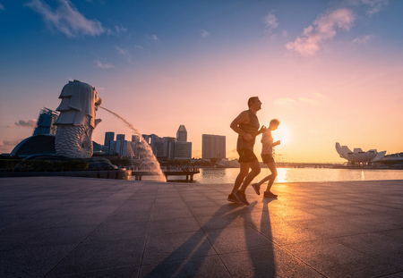 SINGAPORE - APRIL 30, 2018: Unidentified people runnig in Merlion Park and Singapore city skyline at sunrise on April 30, 2018. 스톡 콘텐츠 - 101774359