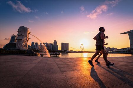SINGAPORE - APRIL 30, 2018: Unidentified people running in Merlion Park and Singapore city skyline at sunrise on April 30, 2018.