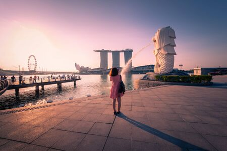 SINGAPORE - APRIL 30, 2018: Unidentified traveller in Merlion Park and Singapore city skyline at sunrise on April 30, 2018.