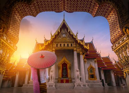 Woman holding traditional red umbrella on the Marble Temple, Wat Benchamabopitr Dusitvanaram at sunrise in Bangkok, Thailand.