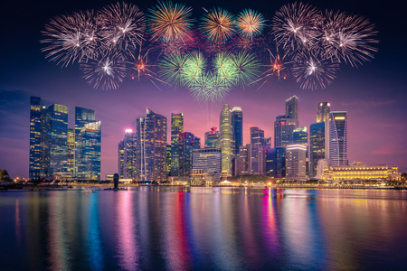 Firework over Singapore Skyline and view of skyscrapers on Marina Bay at twilight time. Stock Photo
