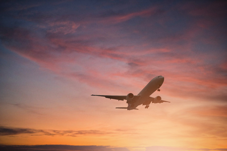 Silhouette of plane fly on sky during sunset. Stock Photo