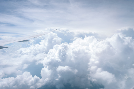 Wing of airplane flying above the clouds in the blue sky background through the window. Stock Photo