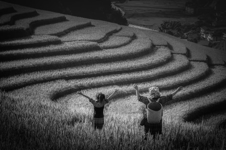 Women farmer and daughter raising arm on Rice fields terraced at sunset in Mu Cang Chai, YenBai, Vietnam. Stock Photo