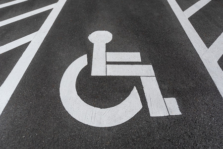handicapped  disabled parking sign painted on the road asphalt.
