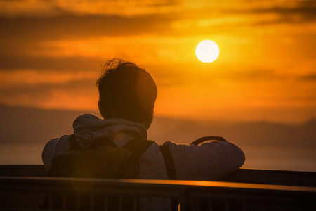 Rear view of Traveler man looking sea at sunset in Shizuoka, Japan. Stock Photo