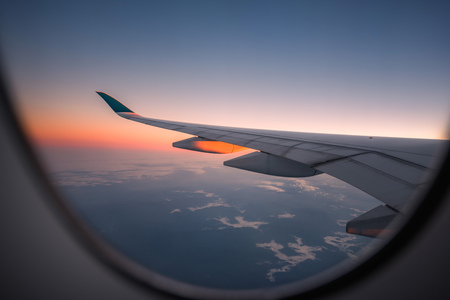 Silhouette wing of an airplane at sunrise view through the window. Stock Photo