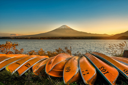 Mt. Fuji over Lake Kawaguchiko with boats at sunset in Fujikawaguchiko, Japan. Editorial