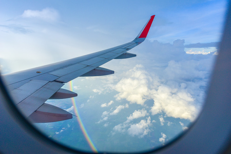 Wing of an airplane flying above the clouds and  rainbow look from cabin window. Stock Photo