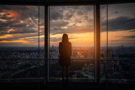 Rear view of Traveler woman looking Tokyo Skyline and view of skyscrapers on the observation deck at sunset in Japan.