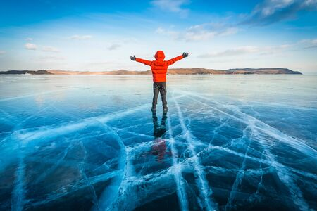 Traveler man wear red clothes and raising arm standing on natural breaking ice in frozen water at Lake Baikal, Siberia, Russia.