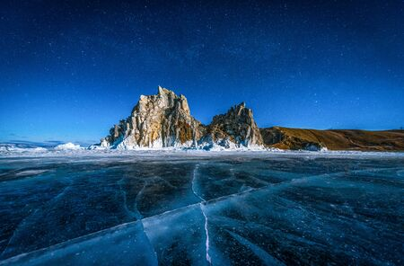 Landscape of Shamanka rock and star on sky with natural breaking ice in frozen water on Lake Baikal, Siberia, Russia.