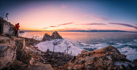 Landscape of Shamanka rock at sunset with natural breaking ice in frozen water on Lake Baikal, Siberia, Russia.