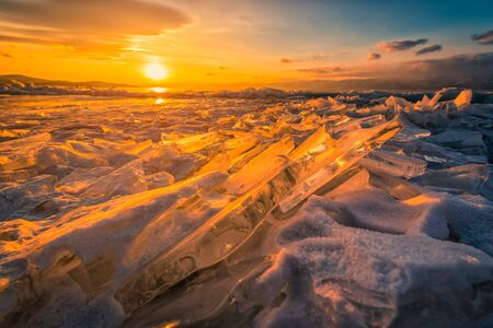 Sunset sky with natural breaking ice over frozen water on Lake Baikal, Siberia, Russia. Reklamní fotografie