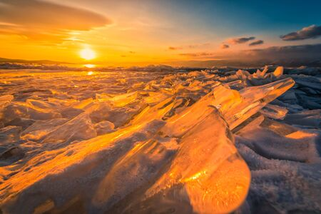 Sunset sky with natural breaking ice over frozen water on Lake Baikal, Siberia, Russia. Stock fotó