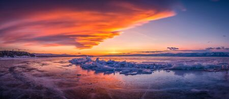 Sunset sky with natural breaking ice over frozen water on Lake Baikal, Siberia, Russia. 免版税图像