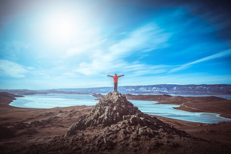 Traveler man wear red clothes and raising arm standing on the peak of mountain near Lake Baikal, Siberia, Russia.