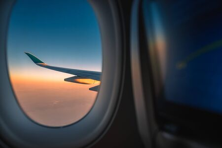 Silhouette wing of an airplane at sunrise view through the window. Reklamní fotografie