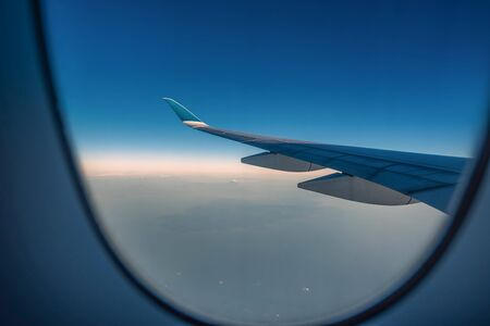 Silhouette wing of an airplane at sunrise view through the window. Stock fotó