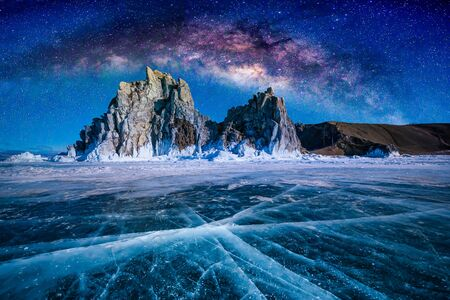 Landscape of Shamanka rock and milky way on sky with natural breaking ice in frozen water on Lake Baikal, Siberia, Russia. Reklamní fotografie