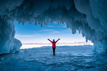 Traveler woman wear red clothes and raising arm standing on frozen water in ice cave at Lake Baikal, Siberia, Russia.