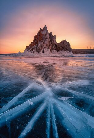 Landscape of Shamanka rock at sunrise with natural breaking ice in frozen water on Lake Baikal, Siberia, Russia.