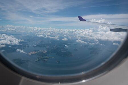 Flügel des Flugzeugs, das über Hong Kong-Stadthintergrund durch das Fenster fliegt.