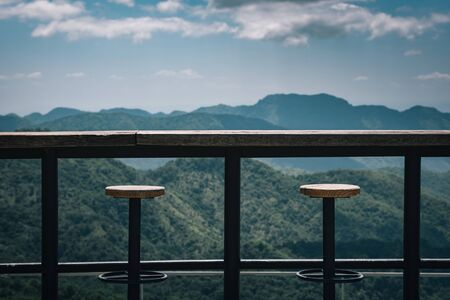 Tables and chairs on the terrace with view mountain and sky. Vintage tone