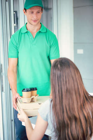 Delivery man employee in green cap t-shirt ready to send delivery food box in front of custom office. Delivery and shopping online concept.