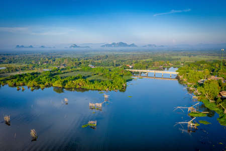 Aerial view image of Traditional square fishnet equipment at sunrise in Pakpra Canal, Phatthalung, Thailand