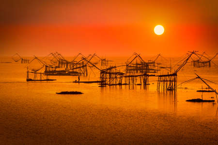 Traditional square fishnet equipment at sunrise in Pakpra Canal, Phatthalung, Thailand
