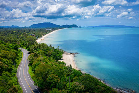 Aerial view of road between coconut palm tree and great ocean at daytime in Nakhon Si Thammarat, Thailand 版權商用圖片