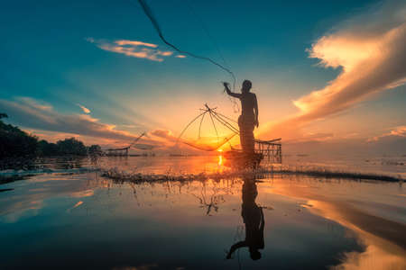 Nakorn Si Thammarat, Thailand-August 16, 2020 : Silhouette Fisherman Fishing Nets on the boat at sunrise in Thailand 新聞圖片