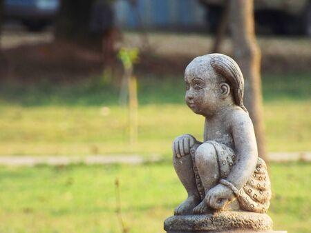 sadly: Statua di un bambino seduto tristemente