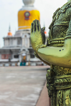Angel statue standing with hands clasped at Wat Phra That Na Dun., Which is a landmark and tourist attraction of Buddhism Mahasarakham Province, Thailand. photo