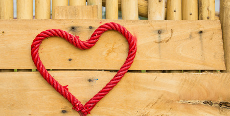 Red heart on a rope tied to a wooden board. Stock Photo