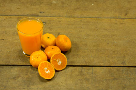 Orange juice placed on the wooden floor 免版税图像
