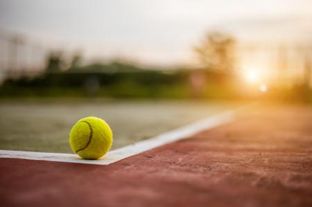 Tennis ball on hard court at sunset Stock Photo