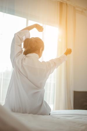 Mujer asiática se despierta por la mañana, sentada en la cama blanca y estirándose, sintiéndose feliz y fresca