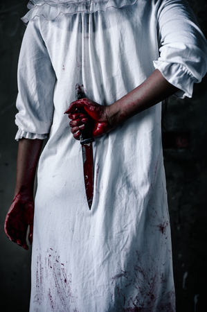 Ghost woman Hold the knife behind. horror of scary fear on hell is monster devil girl in halloween festival concept Stock Photo