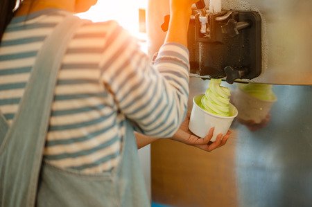 The woman make ice cream from the machine.